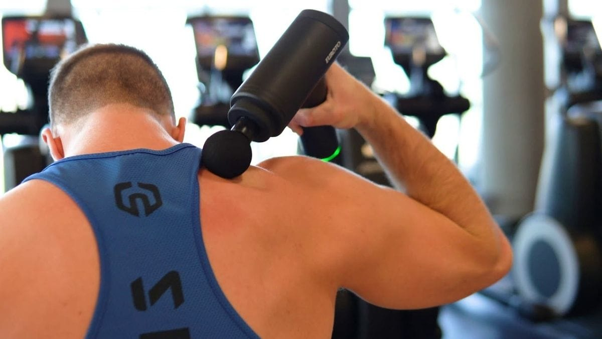 A guy at the gym massaging his shoulders with a black colored portable massage gun.
