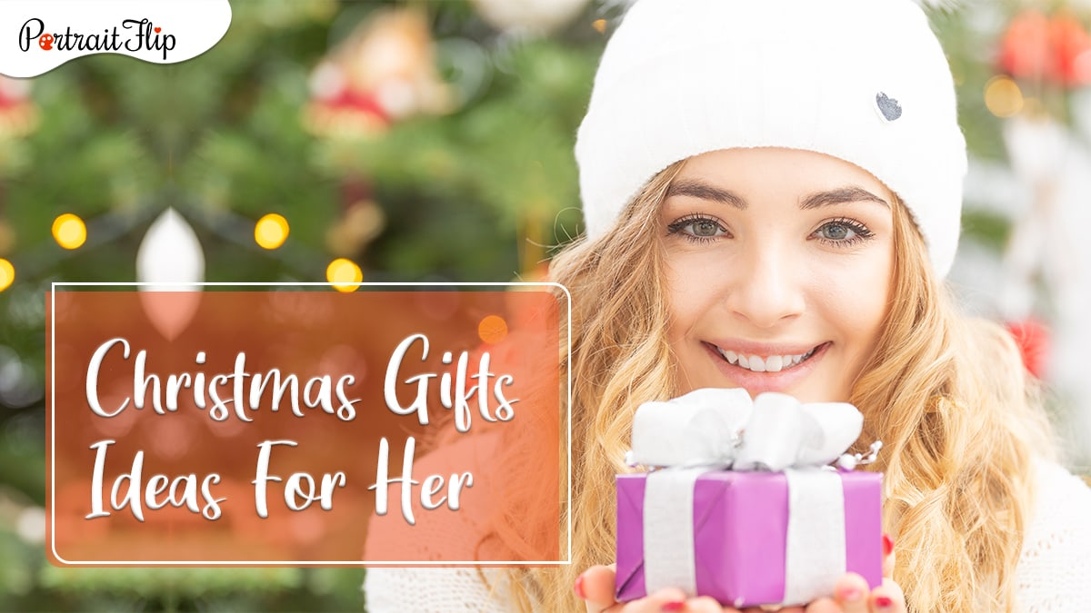 christmas gifts for her: a woman posing with a small gift.