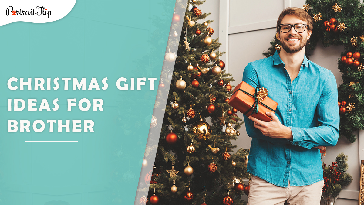 Christmas gift ideas for brother: a man in a blue shirt hold a christmas gift as he poses beside a christmas tree.