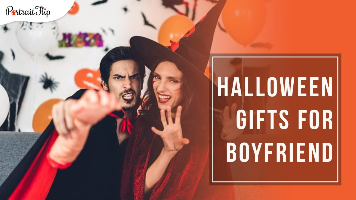A couple in a vampire and witch outfit sitting on a grey couch with Halloween themed wall décor in the background. the guy on the left is holding a fake human hand and the girl is holding both her hands in a scare position. Halloween gifts for boyfriend is written in a block on the right hand side.