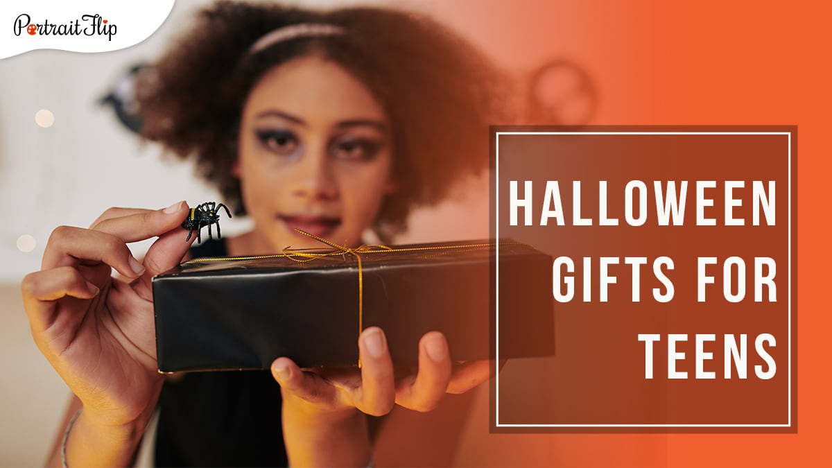 a teenager with puffed hair and spooky makeup holding a toy spider on top of a black gift with golden ribbon with Halloween Gifts for Teens written on a block on the right hand side