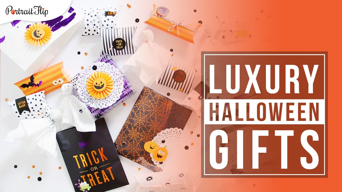 Halloween themed gifts and boxed kept on a table with origami ghosts with orange and black sequins sprinkled around them. Luxury Halloween gifts written in a block on the right hand side.