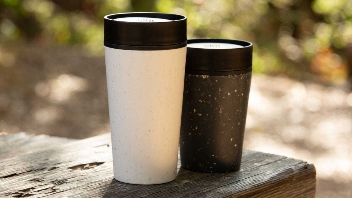 A White Reusable coffee cup and a smaller black colored reusable coffee cup is placed on the wooden block outside.