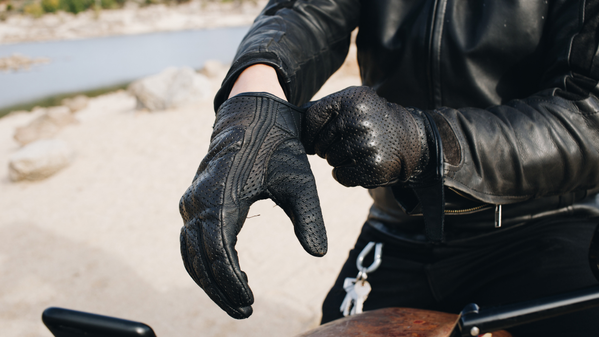 A man wearing his black rider gloves before turning on the vehicle.