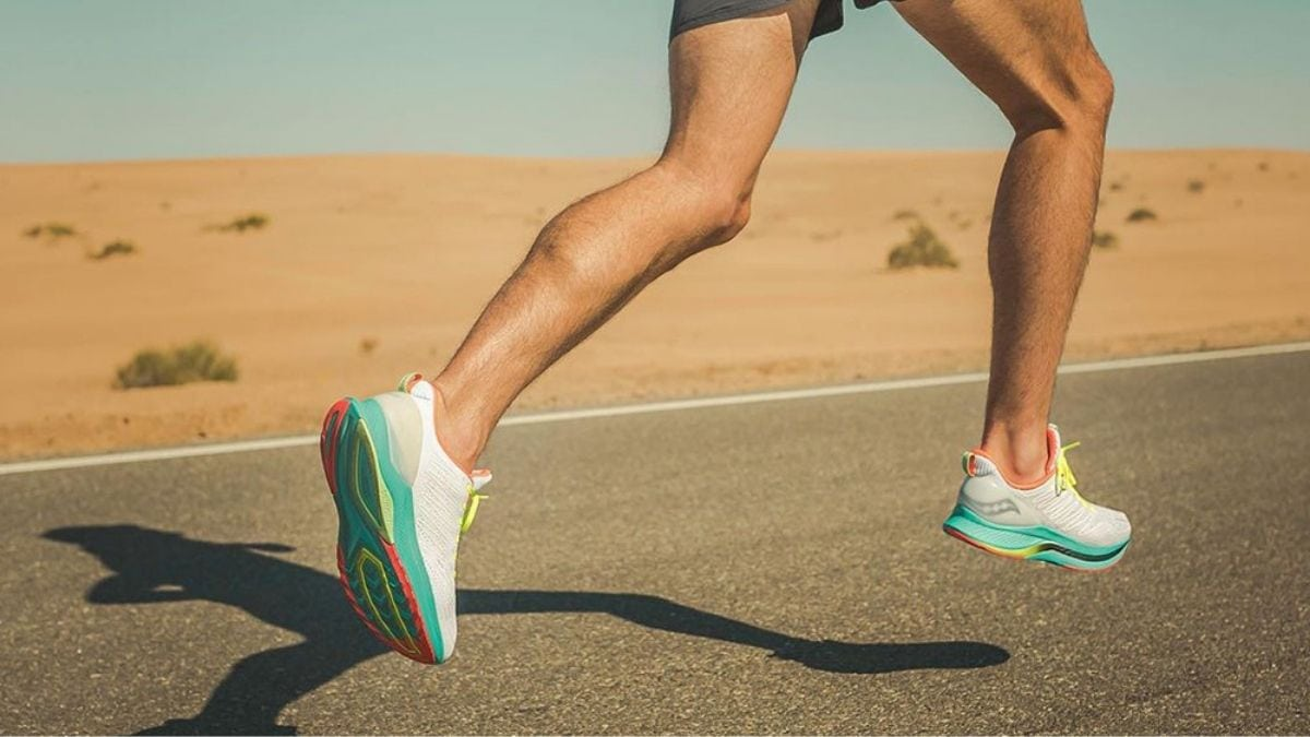 a guy running on a road by the desert wearing white and green running shoes