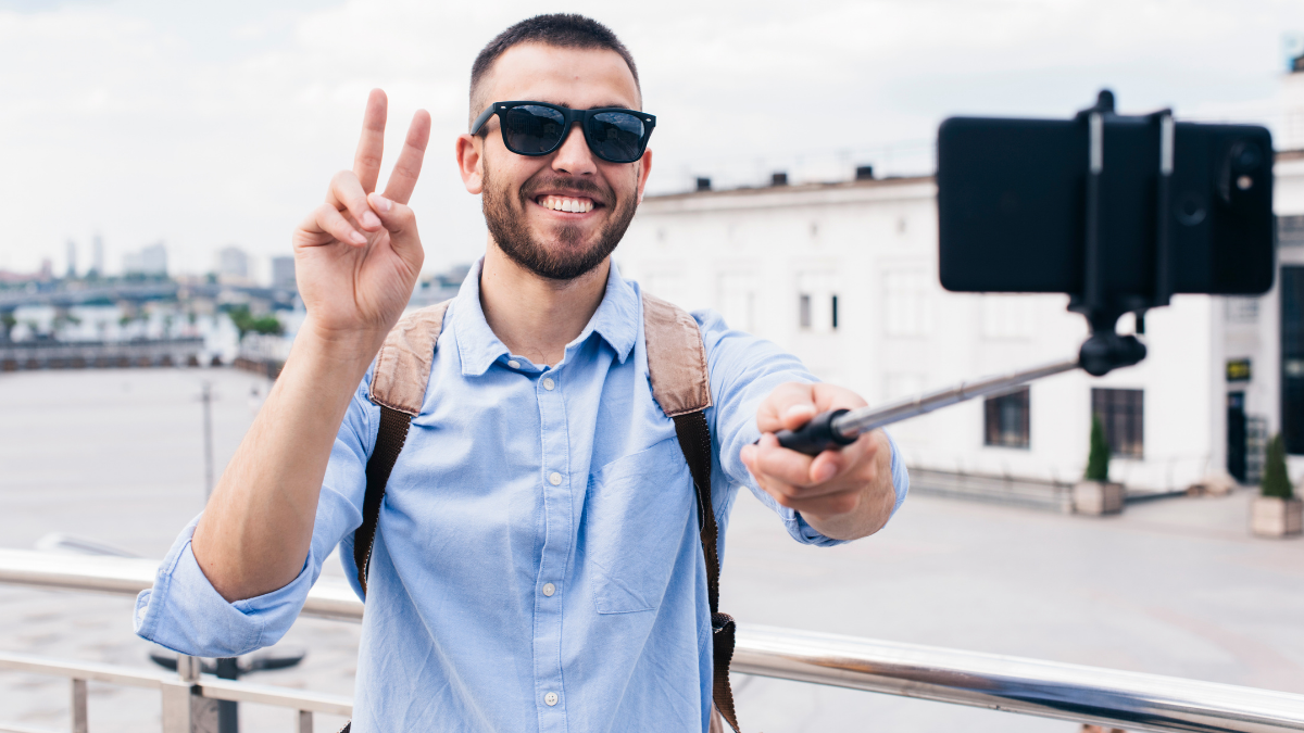 A man showing victory sign while taking a selfie with the help of selfie stand