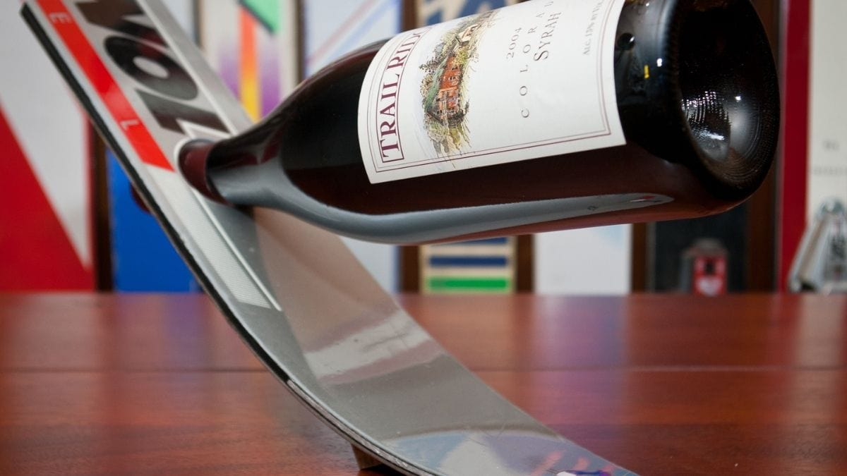 a wine bottle attached to a ski wine rack on a table.