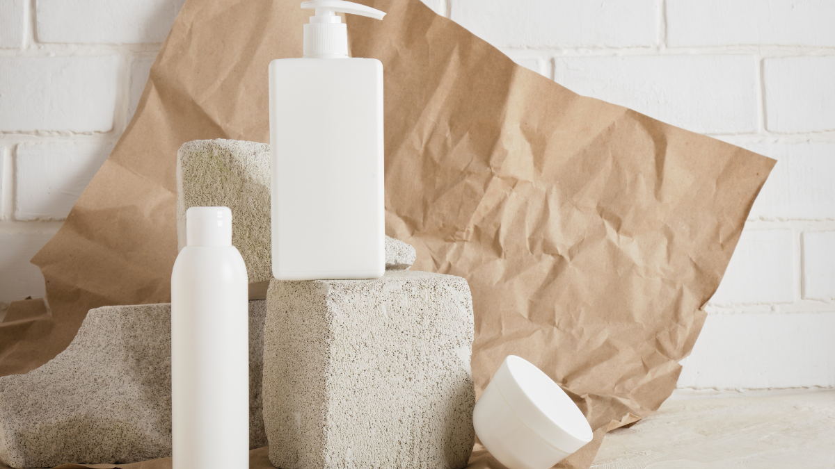 Skincare products are placed on white bricks. There is a brow background and some paper around them.