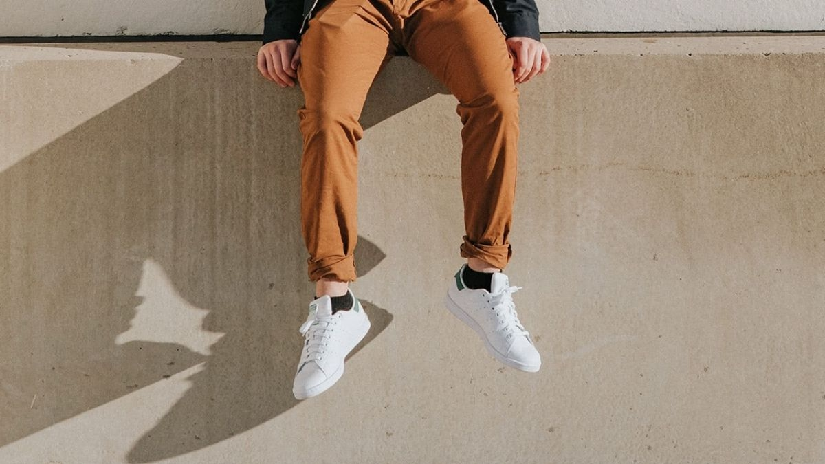 A guy flaunting his white sneakers.