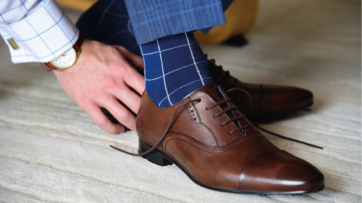A guy wearing blue socks is tying the lace of brown shoes