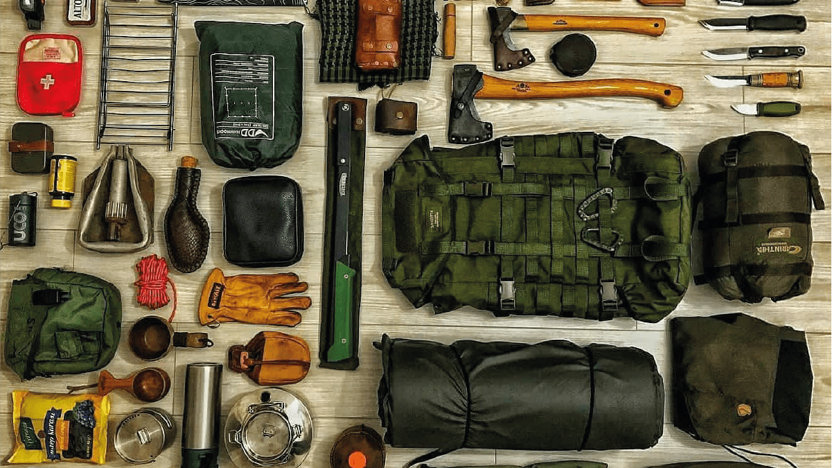 various survival tools including hammer, knives, bagpack, gloves etc are kept on the table
