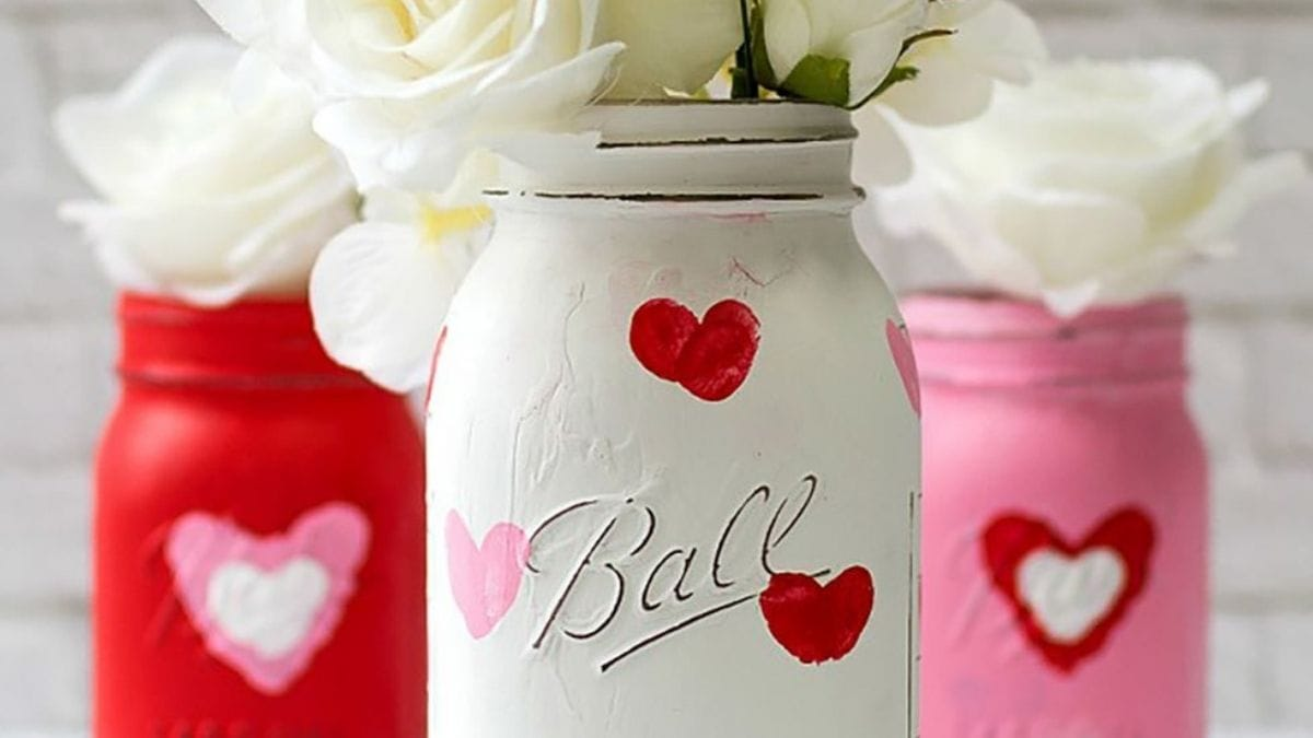 A white colored beautiful jar is placed ahead of two jars which is embellished with pink paper.
