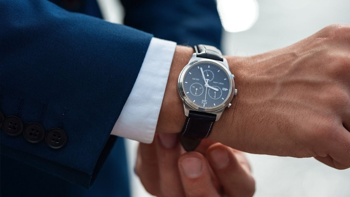 A man in formals showing his timepiece.
