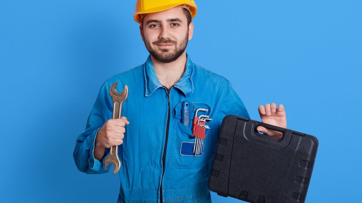 A man is smirking by holding a tool bag in his finger on a blue background.