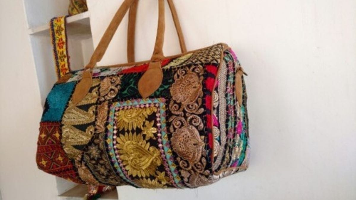 A flower shaped handmade travel bag is hanging.