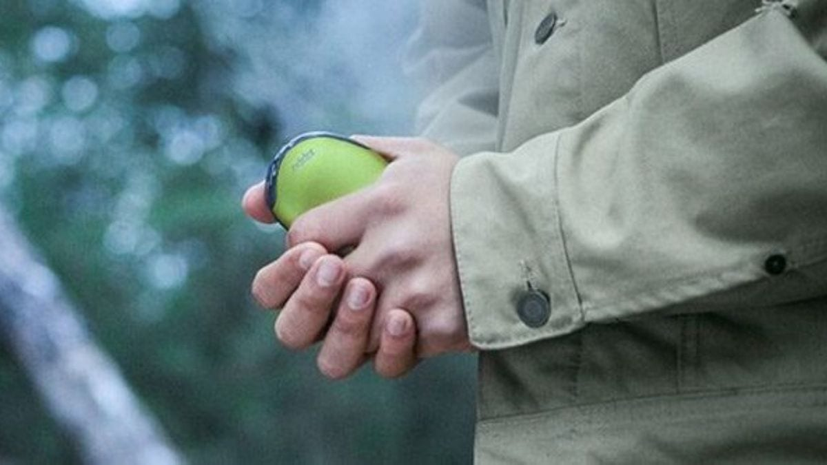 a person holding an USB hand warmer in the cold.