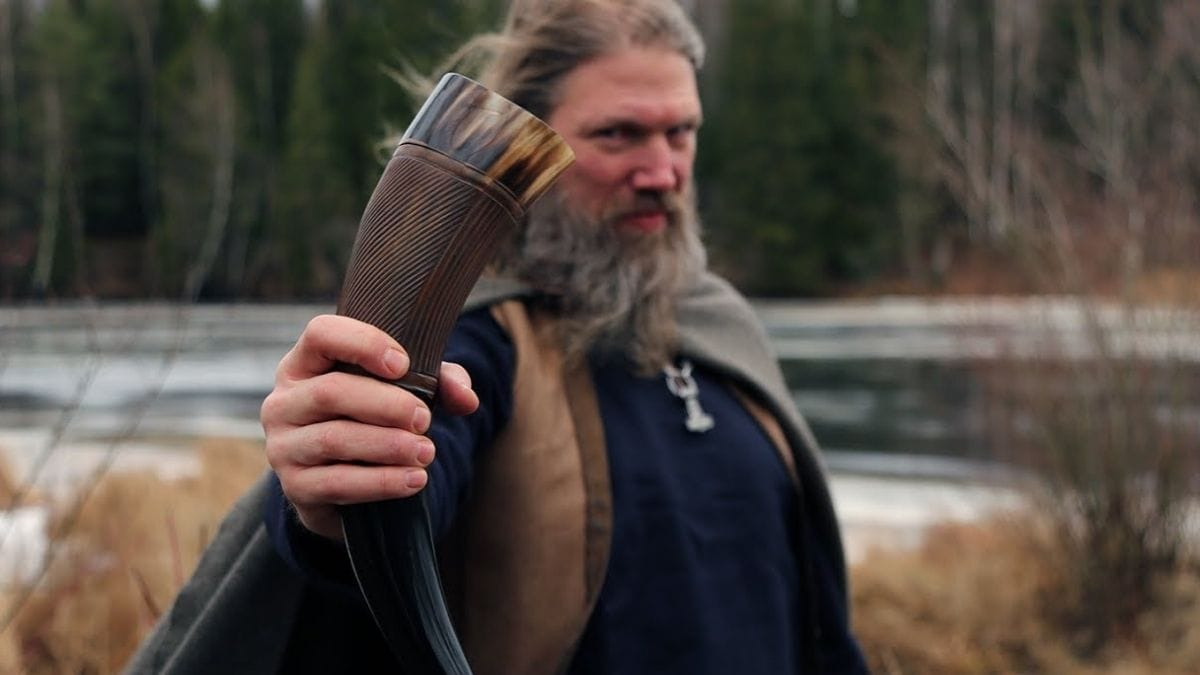 a guy holding a Viking drinking horn in the wild.