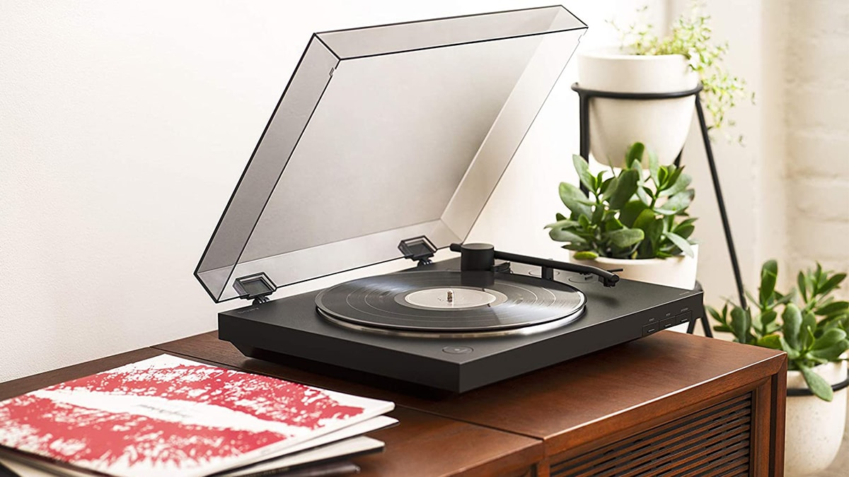 a vinyl player playing music on a table. beside it is a stack of records.