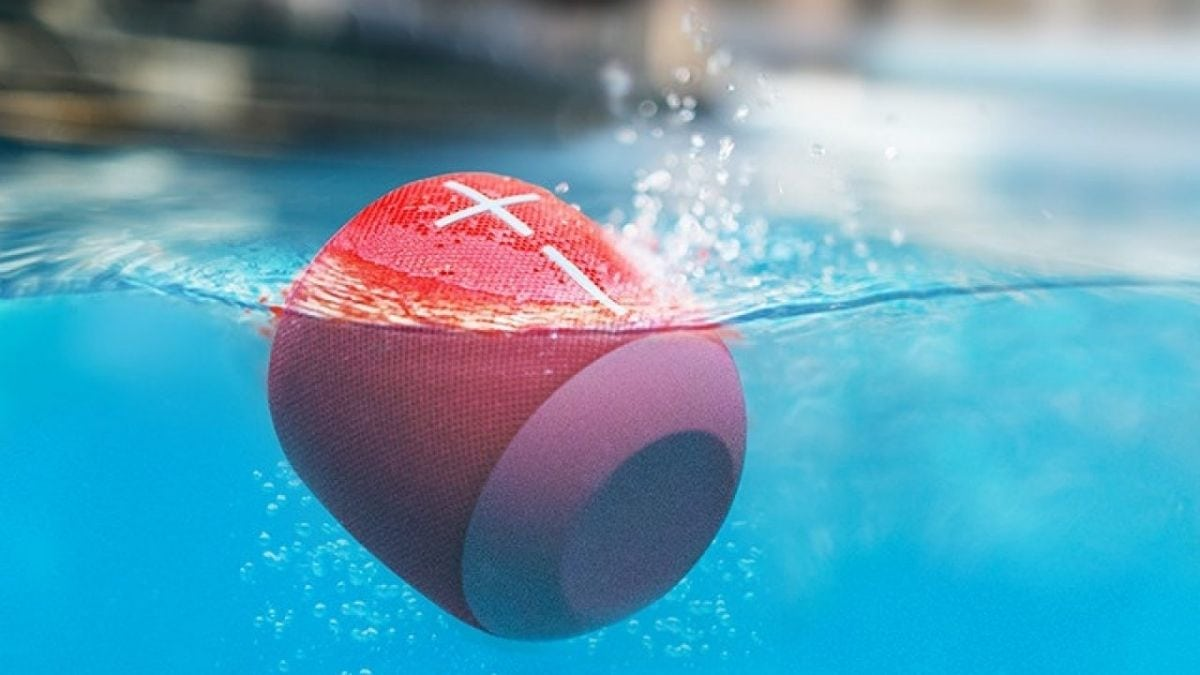 A small red waterproof Bluetooth Speaker floating in the swimming pool.
