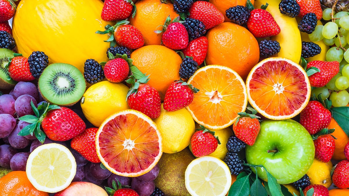 A photo of fruits from above: oranges, mulberry, strawberry, apple, lime, grapes, banana, kiwi