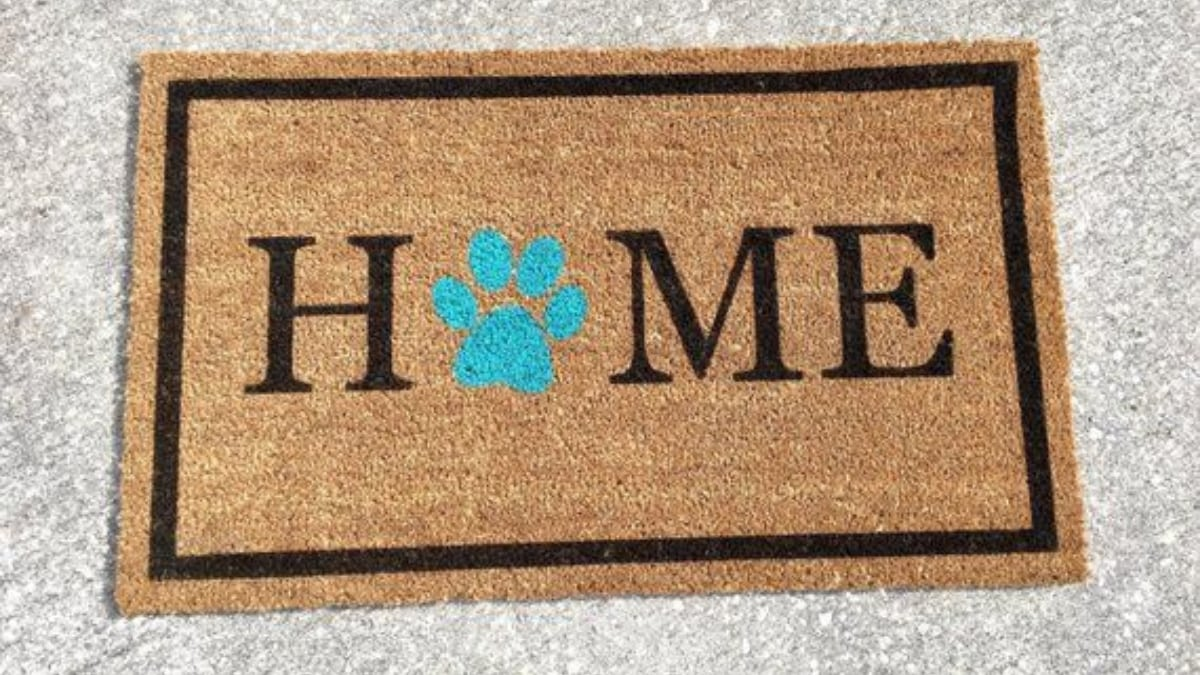 A brown colored welcome mat is placed on the grey surface.