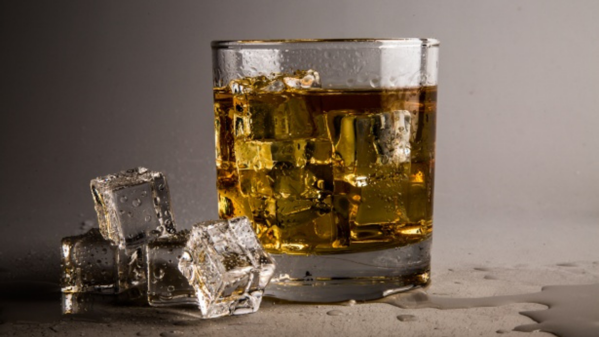 A classic whiskey glass is placed on the plain surface with three ice cubes on its sides.