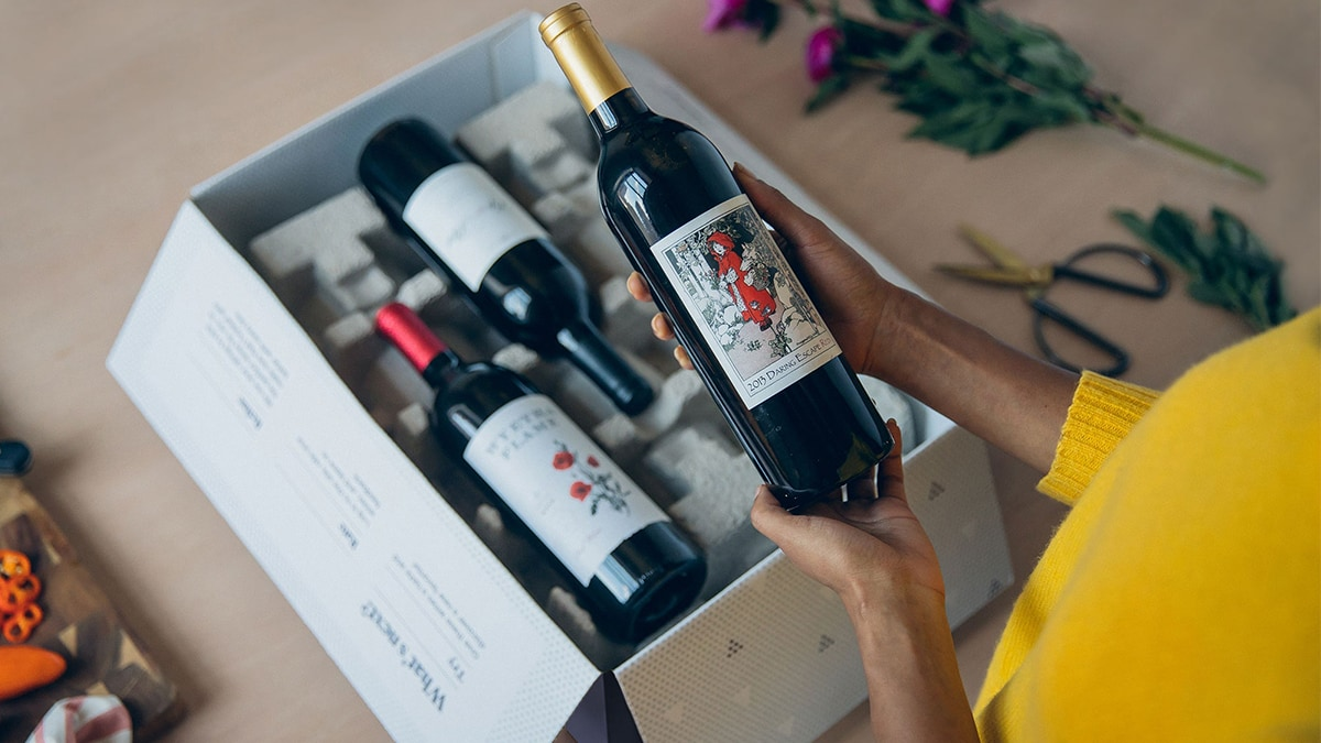 a woman holding a wine bottle form a box.