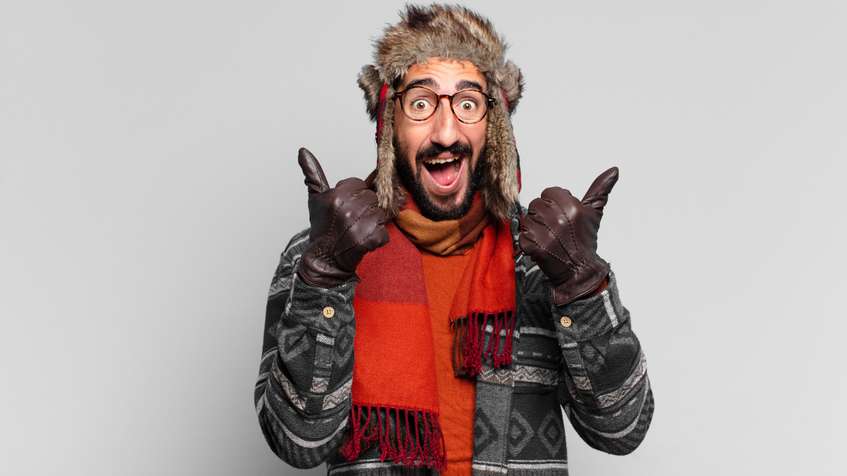A happy man in a black sweater expressing his happiness on wearing a nice winter gloves.