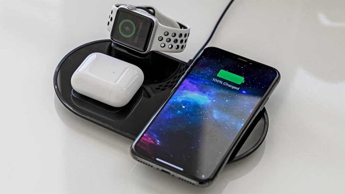 a phone, smartwatch, and wireless airbuds charging on a charging station.