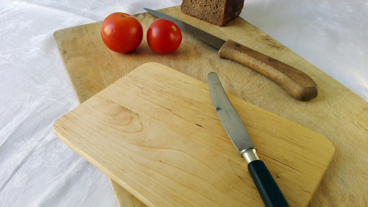 Two top-quality bread boards with some tomatoes and knives on them.