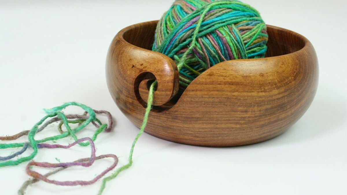 A brown yarn bowl with colorful green and blue yarn.