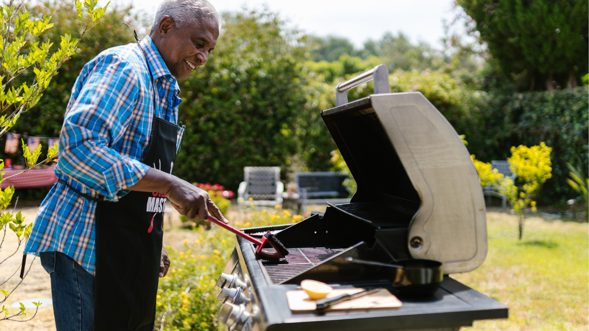 An old man happily Barbequing in a garden.