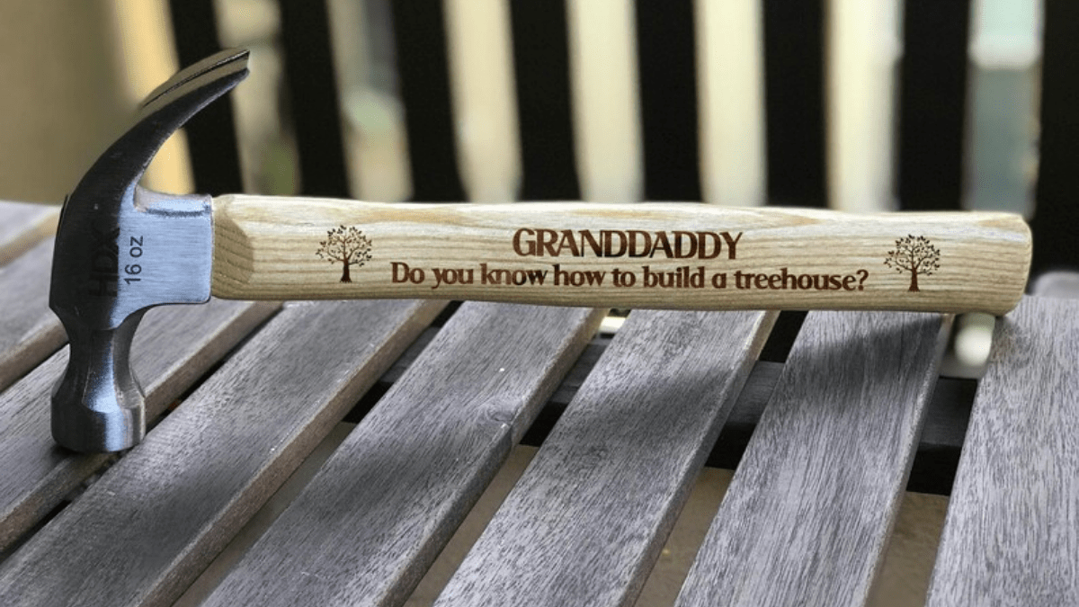 A personalized hammer, with brown wooden handle and metal front. A message engraved for granddad on the wooden handle