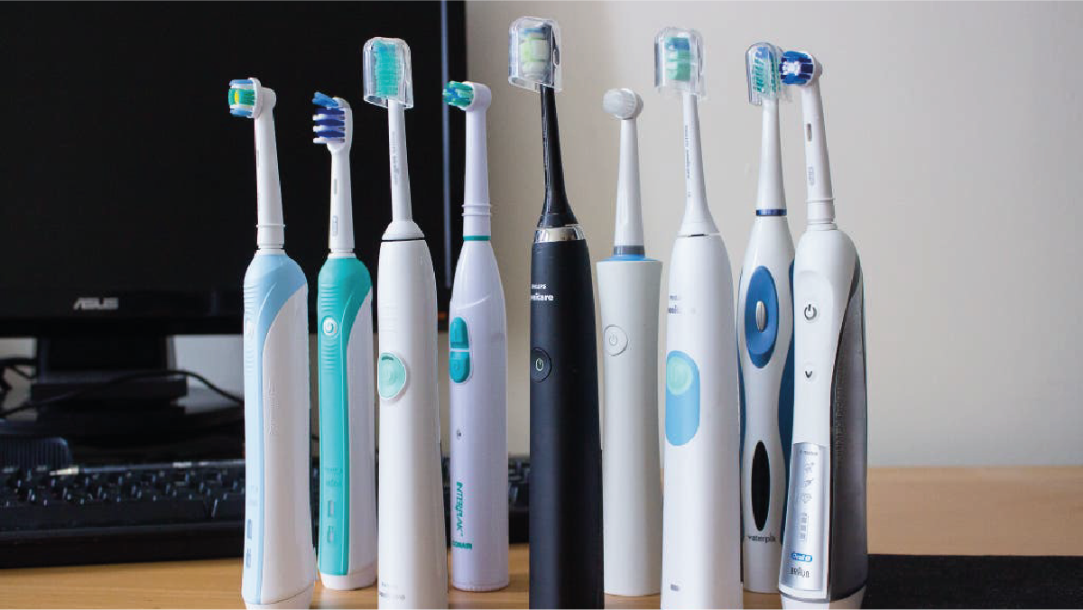 9 different Electric toothbrushes kept near a compute screen