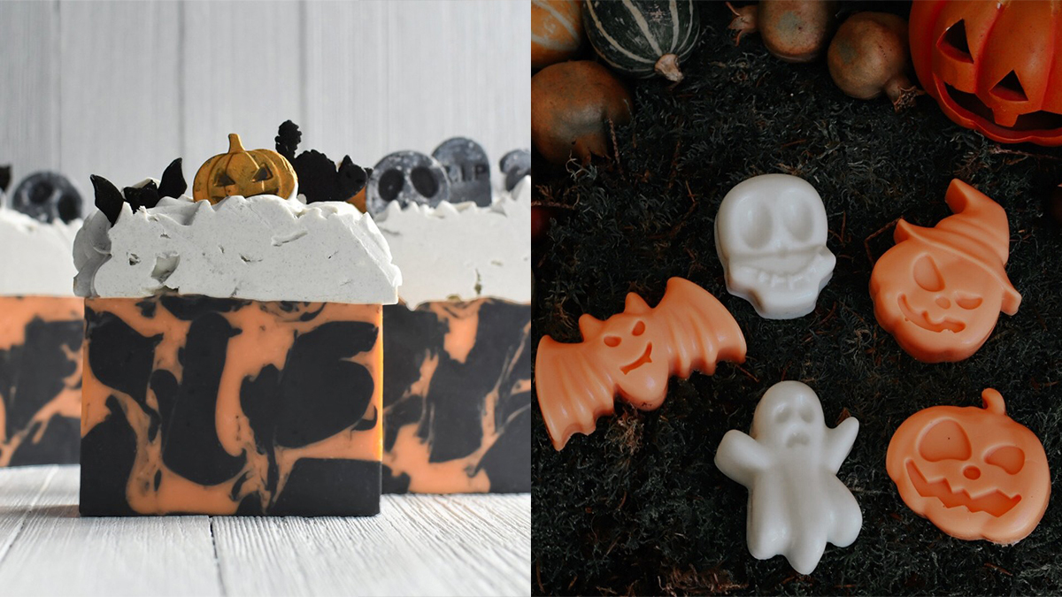 A graveyard themed soap with pumpkin, bat, and a cat as a topper on the left. Right and white colored soaps in the shapes of bat, ghost, skull and Jack-o-Lantern displayed on the ground.