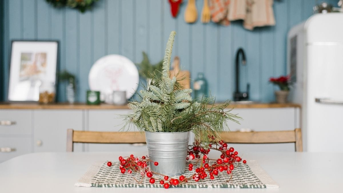 A beautiful yet small Christmas vase is placed on the white table in the pantry.
