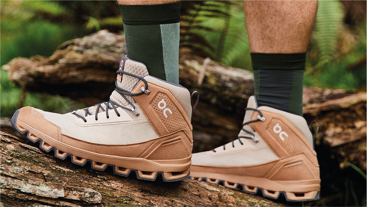 a man stepped up on a big wooden log while wearing brown hiking shoes.