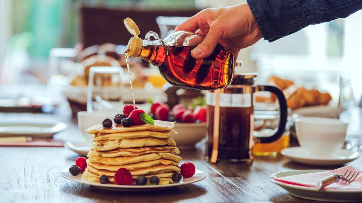 a guy pouring mapple syrup on a pancake with strawberries on a breakfast table.