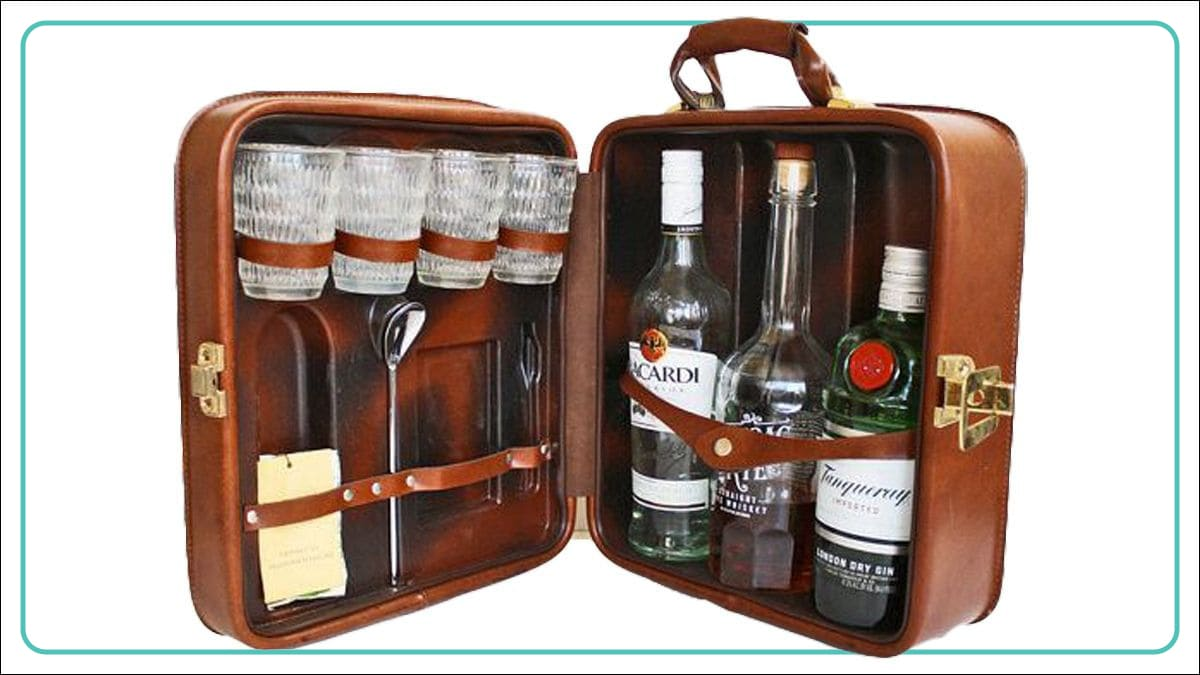 a portable brown colored bar set with glasses, spoon, whiskey, bacardi, stirrer and other alcohol drinks.