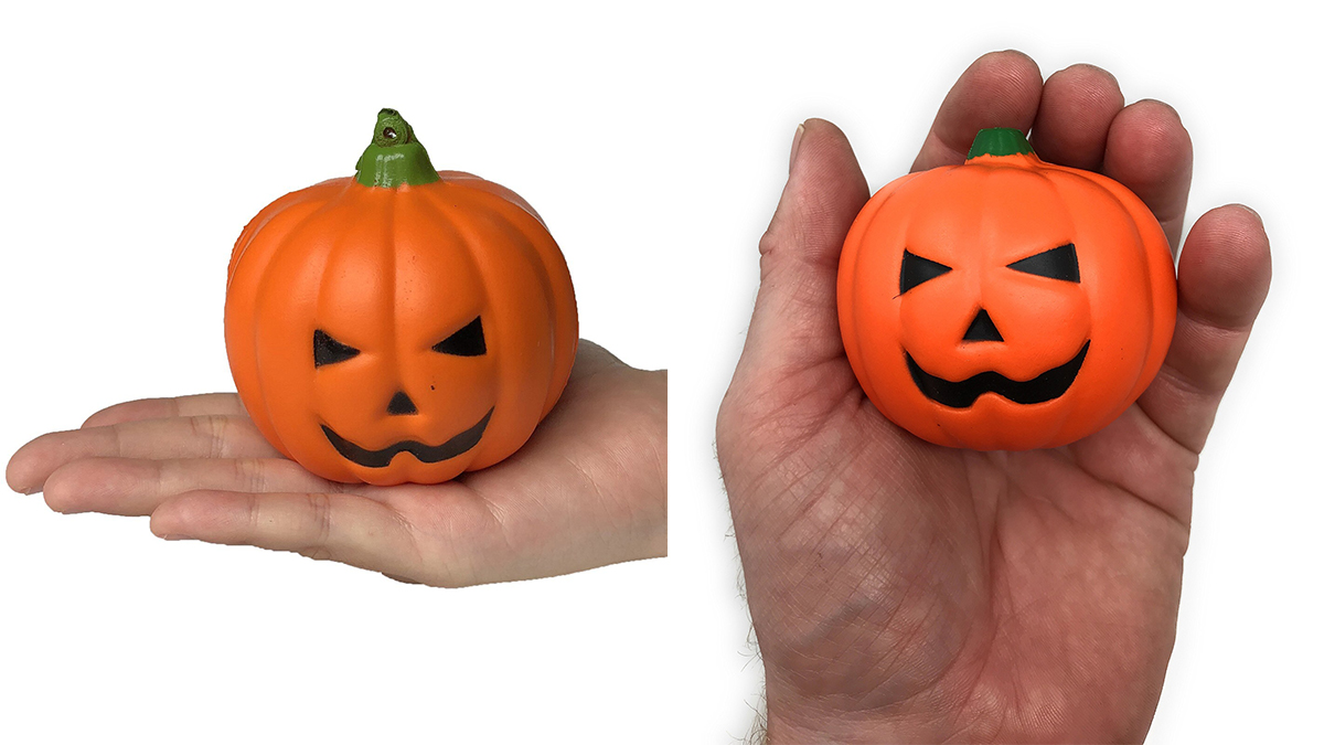2 hands holding a pumpkin shaped stress ball each, a gift that can be given to coworkers on Halloween.