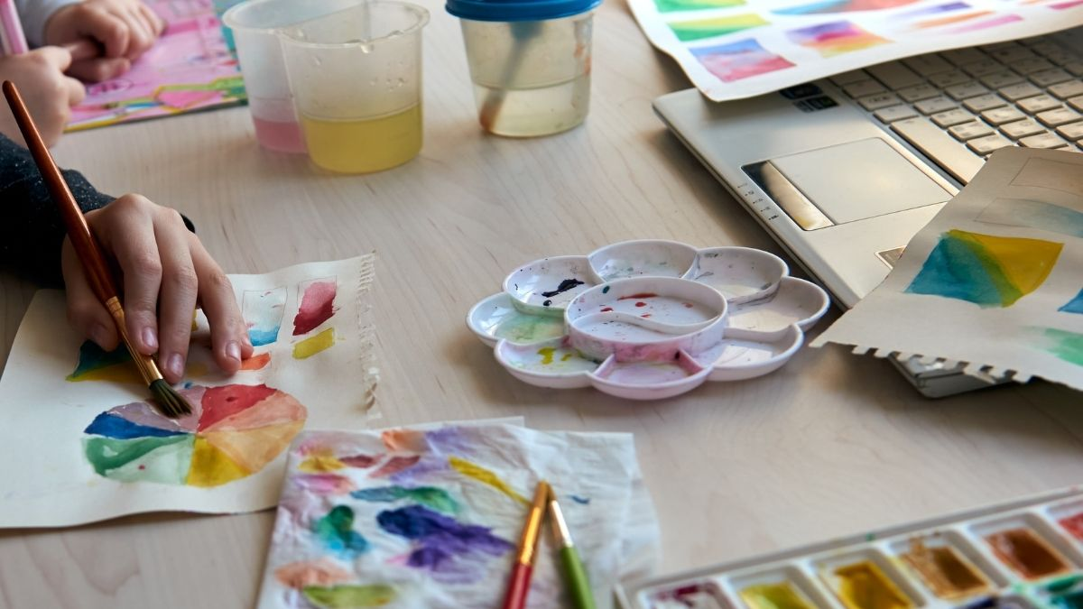 A desk cluttered with watercolor painting supplies, a laptop, water glasses, and a hand painting watercolor painting on a paper.