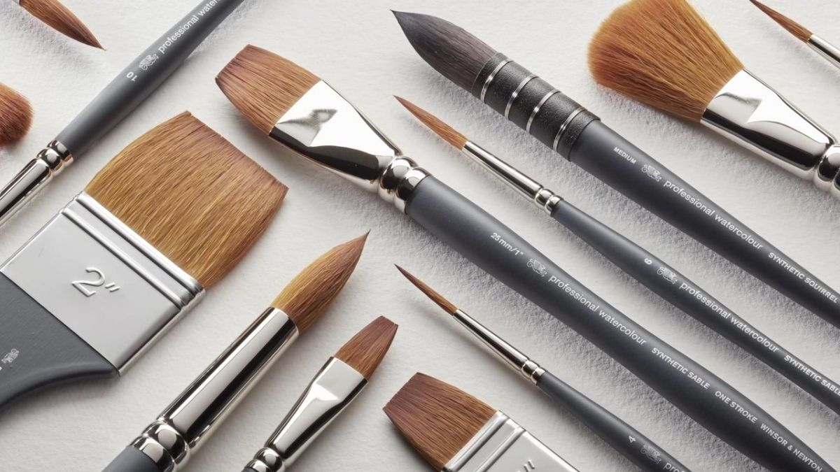 Different types of watercolor paint brushes on a white table.