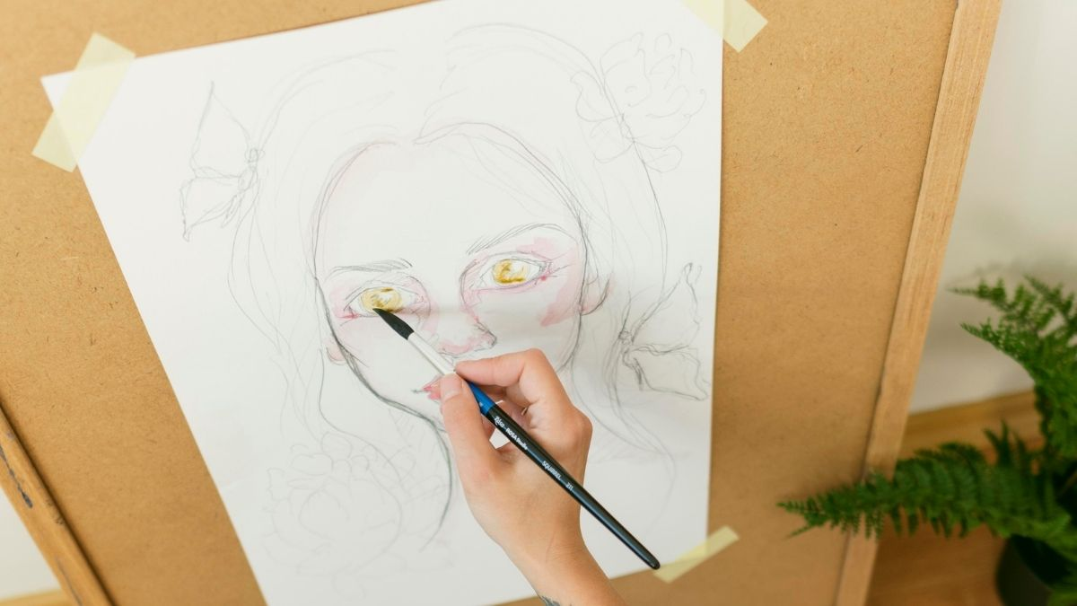 A hand painting watercolor after making an outline with a pencil.