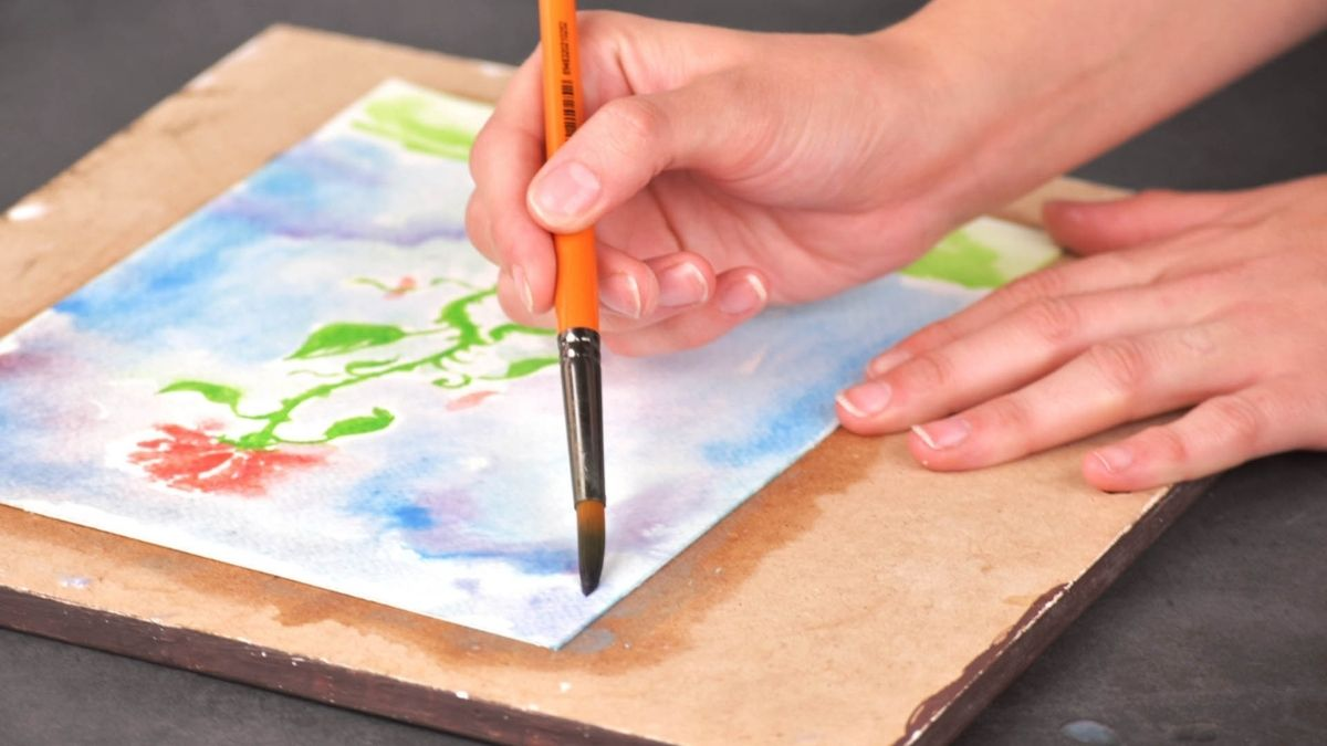 A hand holding a soaked paint brush and painting watercolor on a cubicle wooden board.