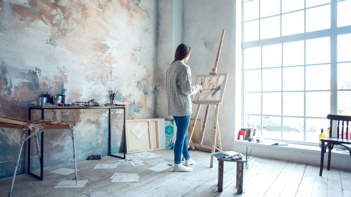 A woman painting in her studio and making use of good lighting to her benefit.